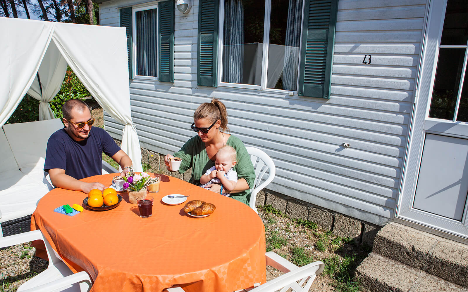 Family sitting at table outside holiday home