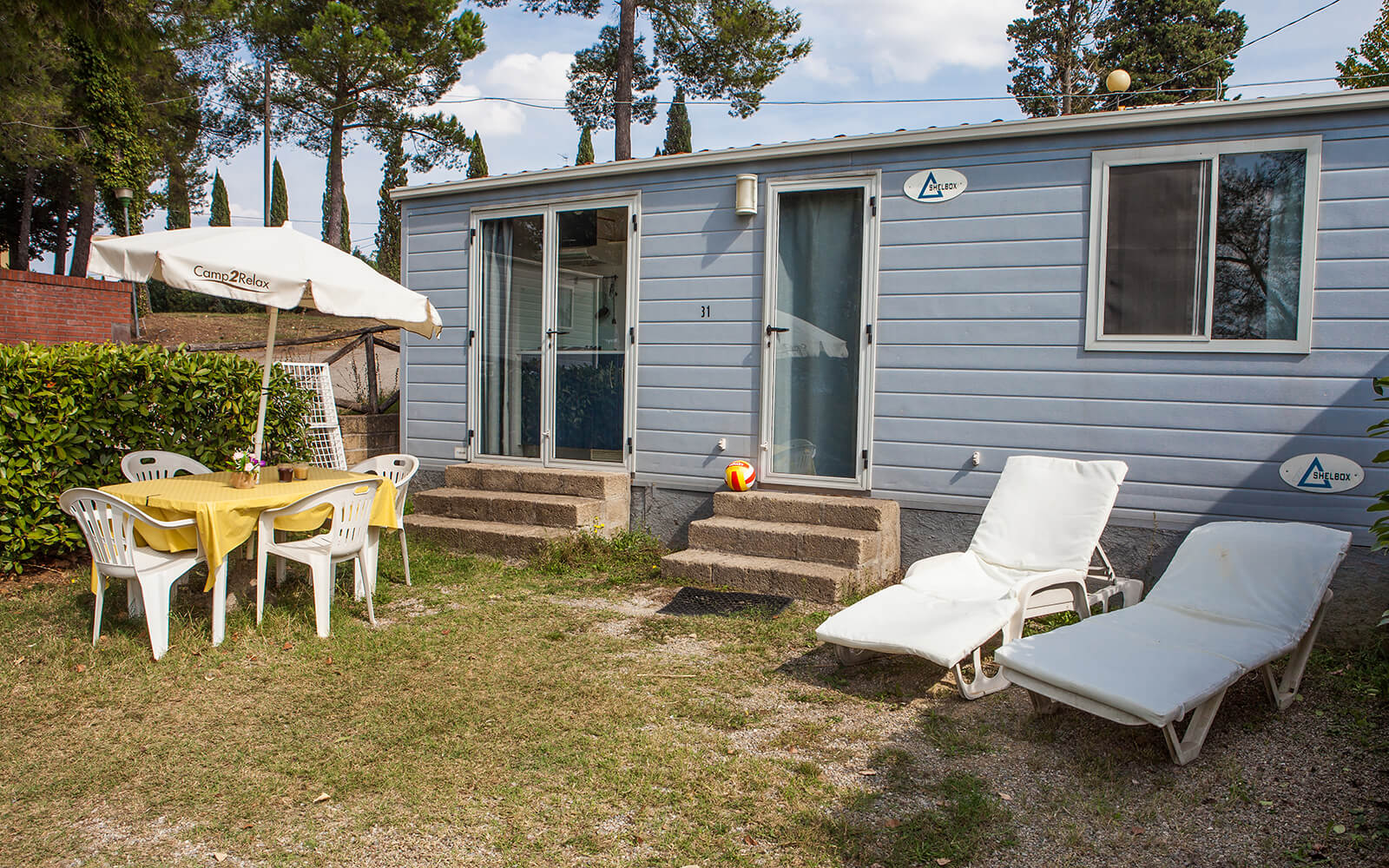 Table and sun loungers outside Comfort mobile home